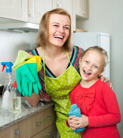 tidy: Portrait of cheerful smiling little daughter and mother tidy up at home kitchen