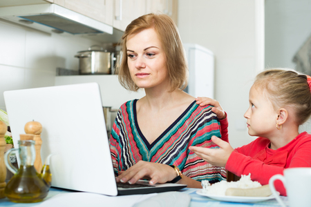 occupied: Occupied woman working from home, little daughter asking for attention