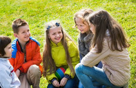 blabbing: Group of happy positive children laughing and chatting in spring park Stock Photo