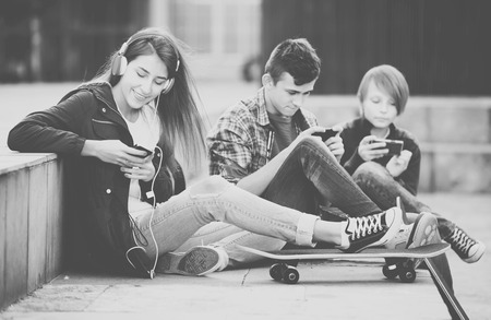 16s: Teenage males and girl relaxing with smartphones on the street Stock Photo