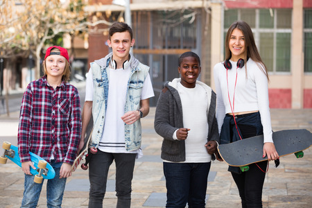 blabbing: Group of happy smiling teens with bikes and skateboards outdoors