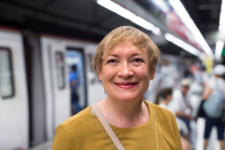 retiree: portrait of cheerful smiling retiree woman passenger in public train station in city Stock Photo