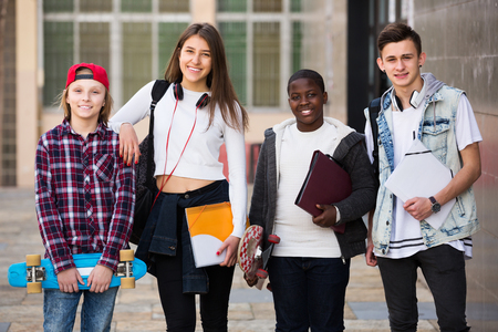 studing: Four smiling young teenage students close to university