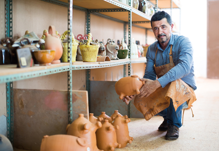 faience: Mature male artisan in apron posing with terra-cotta pigs  in ceramics workshop