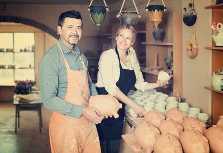 workroom: Portrait of two adult positive craftsmen with ceramic crockery in hands in studio