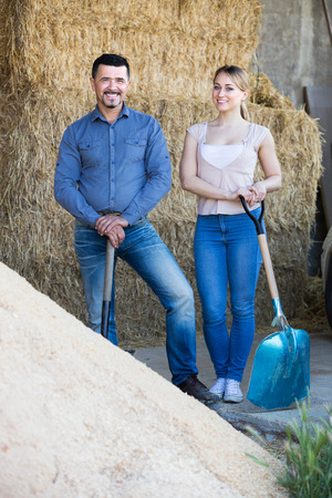 hangar: Man and young woman standing with metallic spades in hangar with sand pile