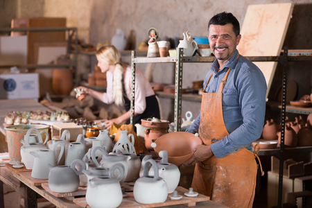 artisans: Artisans in ceramics workroom with pottery wheel and various clay vessels