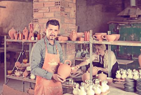 alfarero: Smiling american man potter holding ceramic vessels in atelier
