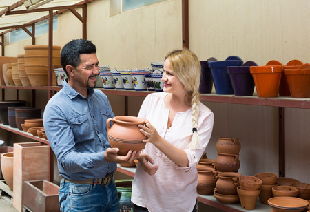 faience: portrait of happy man and woman shopping ceramic utensil in boutique