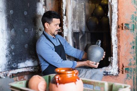 atelier: Cheerful friendly smiling craftsman carrying fresh baked black glazed vessel in ceramics atelier