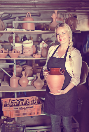 potter: Young woman potter in apron carrying ceramic vessels in atelier Stock Photo