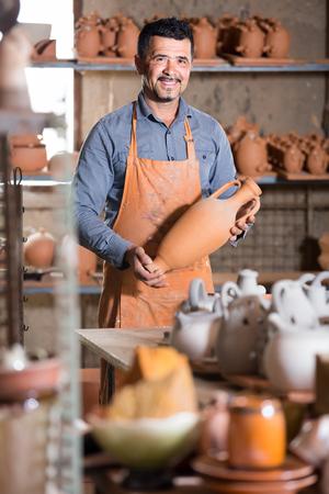 alfarero: Sonriendo hombre español alfarero sosteniendo vasijas de cerámica en el taller Foto de archivo