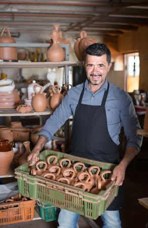 atelier: happy man potter holding ceramic vessels in atelier
