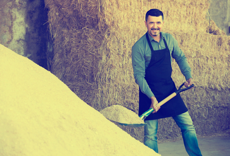 excavating: Mature happy male worker excavating sand using shovel in farm housing