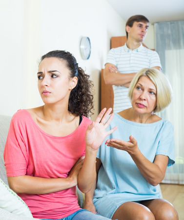 Adult girl having quarrel with husband and mother-in-law Stock Photo