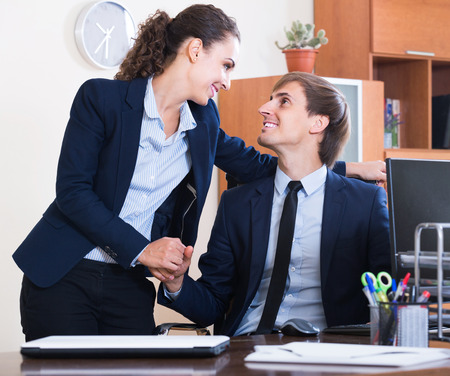 Top manager flirting with happy european adult subordinate official at workplace