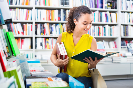 publishers: Smiling charming glad woman standing with open in publishers store Stock Photo