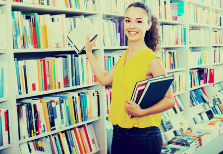 textbooks: portrait of cheerful smiling young brunette woman picking textbooks for school in book shop