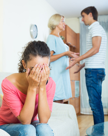 Frustrated young woman taking hard argue between husband and mother