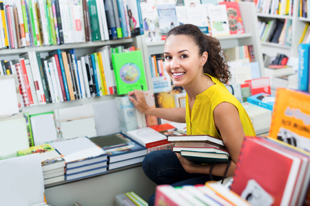 publishers: Young cheerful woman student choosing books in hard cover in bookstore