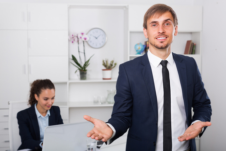 glad: glad business male assistant wearing formalwear standing in company office Stock Photo