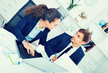 diligente: Dos asistentes masculinos y femeninos de negocios contenta diligentes desgasta la ropa formal que tiene conversación trabajo en la oficina de empresa