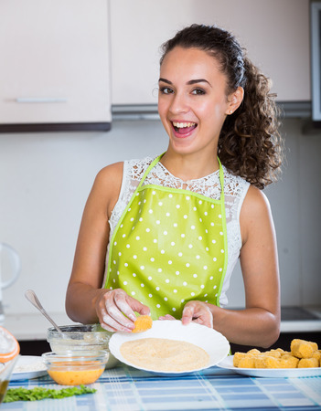 crocchette: Young woman rolling filled croquettes at kitchen table