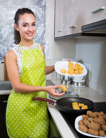 Cheerful girl frying delicious crocchette in pan at home Stockfoto
