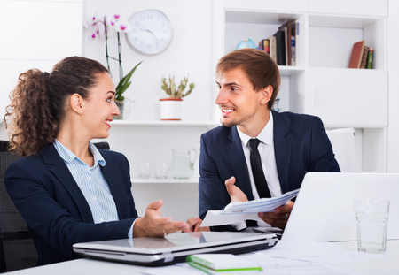 formalwear: Two cheerful glad smiling business male and female assistants wearing formalwear having work conversation in company office