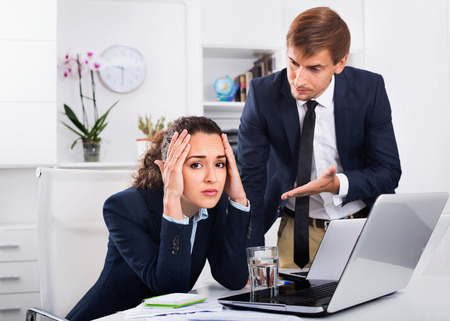 dreary: Sad dreary  subordinate woman being accused to making mistake by man colleague in company office Stock Photo