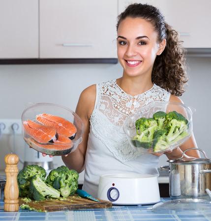 jorobado: Feliz mujer joven vapor salmón y verduras en la cocina doméstica
