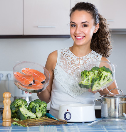 jorobado: Happy young woman steaming salmon and vegetables in domestic kitchen
