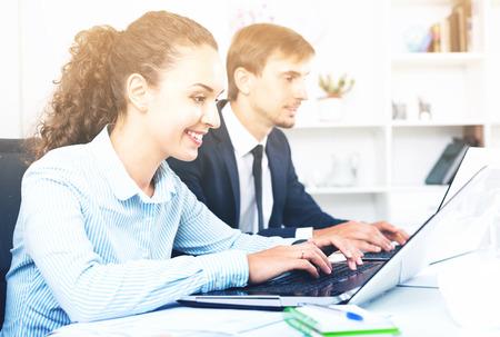 formalwear: Glad friendly  business female assistant wearing formalwear using laptop in company office