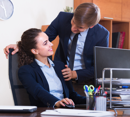 molestation: Sexual harassment in office: smiling boss flirting with employee at workplace Stock Photo