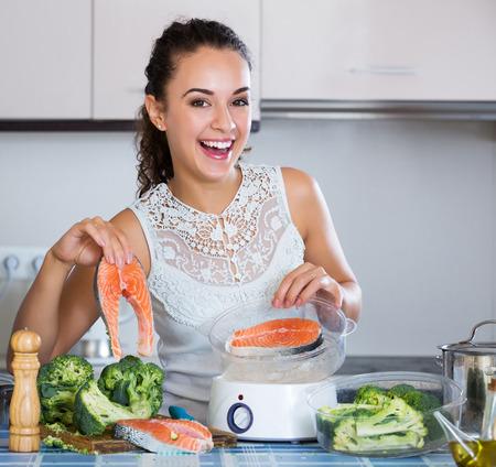 jorobado: truchas jóvenes cocina a la mujer feliz en vapor para el almuerzo saludable Foto de archivo