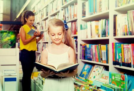 chosen: Glad girl in school age looking in open chosen book in shop