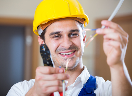 Professional electrician working with wires at client home Stock Photo