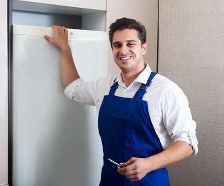 refrigerator kitchen: Happy adult handyman repairing refrigerator in kitchen Stock Photo