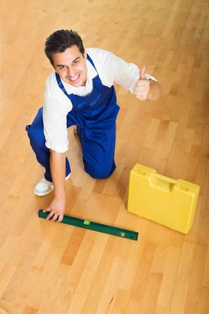 floor level: Positive professional builder checking floor with spirit level indoors