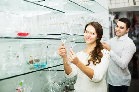 utensilios de cocina: Young smiling family couple buying glassware in cookware shop