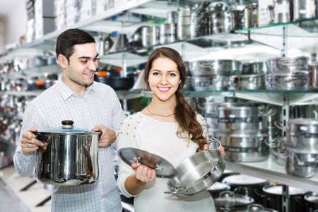 utensilios de cocina: par ruso joven elige sartenes en la tienda de utensilios de cocina