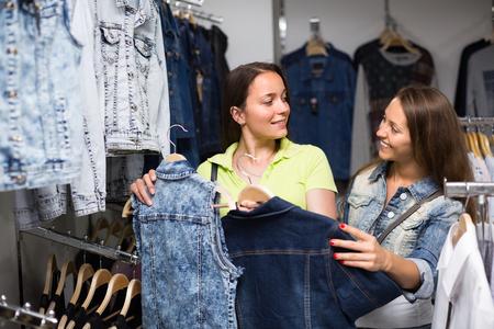 coatee: Happy young smiling women choosing denim jacket in shop Stock Photo