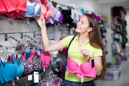 brassiere: Young attractive woman buying the brassiere in clothing store