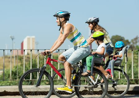 Active young family of four cycling on street road in summer day
