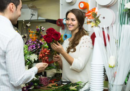 flower seller: Woman seller helping to pick floral bouquet of flowers man client at flower shop