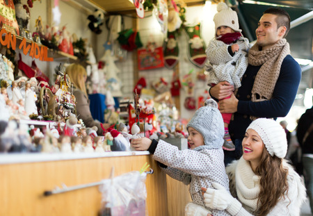 Happy family choosing Christmas decoration at Christmas market. Focus on woman Stock Photo