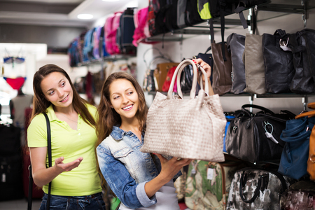 leather bag: Two young women choosing leather bag in shop Stock Photo