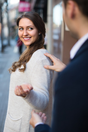 sidewalk talk: Young man flirting with smiling longhaired girl at the street