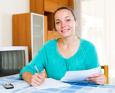 filling out: Beautiful girl filling out tax forms while sitting at her desk