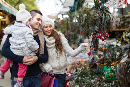 Young smiling parents with little daughter at counter with Poinsettia. Shallow focus